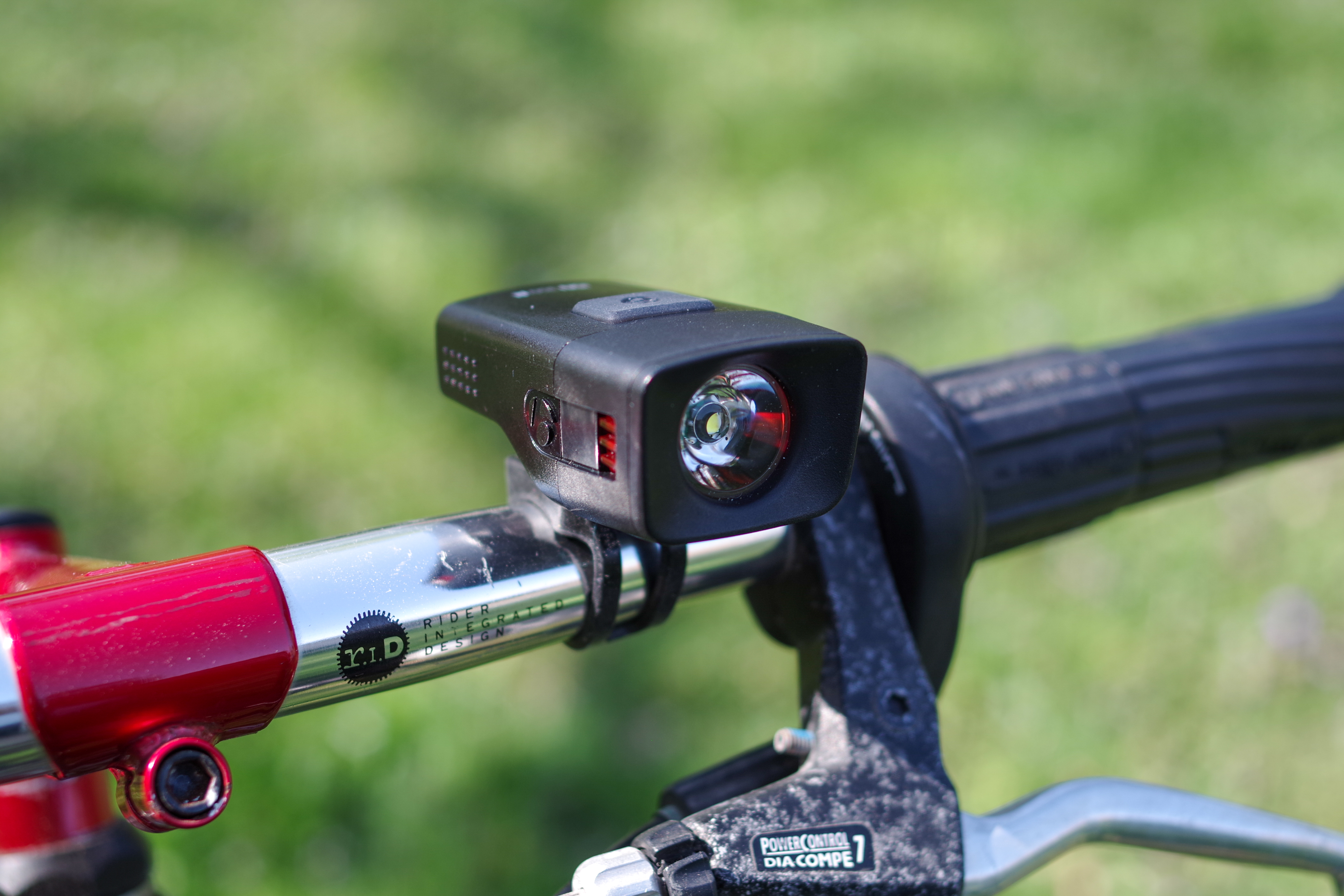 A bicycle headlight on the handle bars of a bicycle. This headlight and bicycle are available for rent through Jill + Ian's bicycle rentals. Photo © Jillian Regan 2018